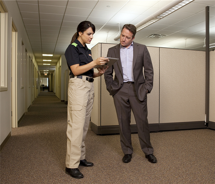 SERVPRO employee standing with man in suit in an office setting